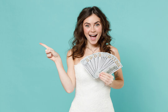 Excited bride woman in white wedding dress hold fan cash money in dollar banknotes point index finger aside isolated on blue turquoise background studio portrait. Ceremony celebration party concept.