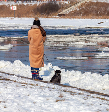Girl with a dog on the river bank in winter.
