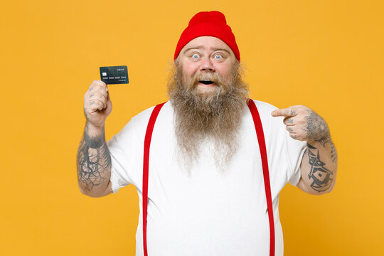 Fat pudge obese chubby overweight tattooed bearded rich surprised man 30s has big belly in white t-shirt red hat suspenders point index finger on credit bank card isolated on yellow background studio.