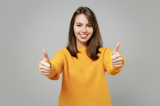 Young smiling happy positive satisfied attractive woman 20s in casual knitted yellow sweater show thumbs up like gesture isolated on grey color background studio portrait. People lifestyle concept.