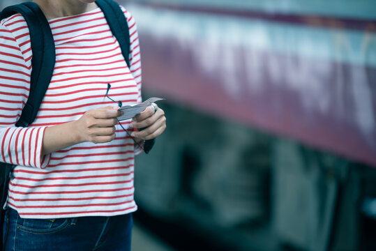 Selected focus on women hands holding a train ticker while standing on train platform waiting for her trip.