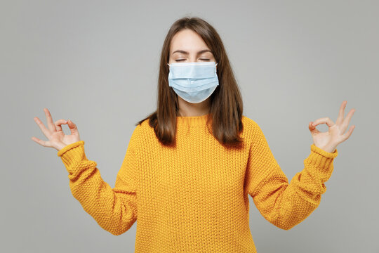 Young woman in yellow sweater in sterile face mask to safe from coronavirus virus covid-19, pandemic quarantine meditating try to relax om yoga gesture isolated on grey background studio portrait..