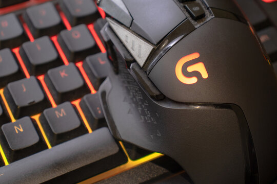 Logitech g502 hero gaming mouse on red illuminated gaming keyboard, close up shot. devices to play on the pc. Verona, 08-02-21