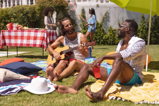 Two diverse male friends playing guitar and smiling at a pool party