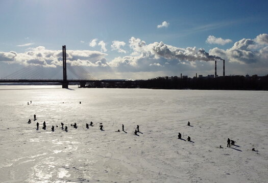 People fish on the frozen Dnipro river in Kyiv