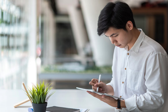 Image side view of an young Asian man work on a tablet in modern office.