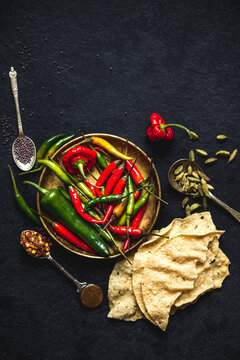 Indian cooking ingredients: chilli peppers, cardamom, black mustard seeds, poppadoms