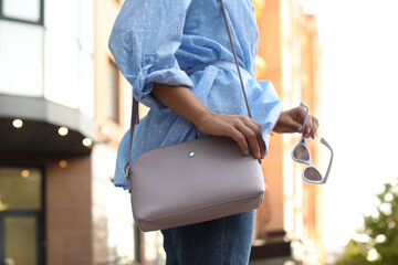 Young woman with stylish bag and sunglasses on city street, closeup