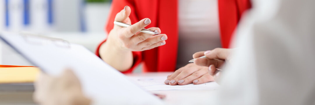 Businesswoman holding ballpoint pen in hands and talking with colleague in office closeup. Development of business plans concept