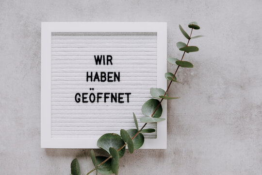 Door sign Wir Haben Geöffnet meaning We Are Open in German language. for small business and shops. White letterboard with words in German and eucalyptus twig. View from above, copy space.