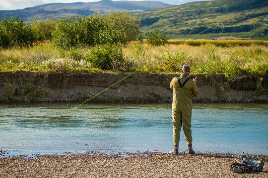 Fly fisherman reeling in a large fish on the Alaska Peninsula.