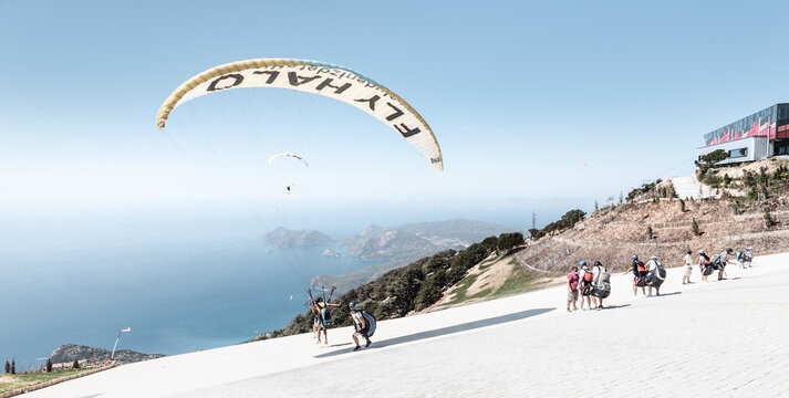 09 September 2020, Babadag, Oludeniz, Turkey: Many paragliding adventurers takeoff in tandem with instructor after a short training session for recreational flight and descent to the sea