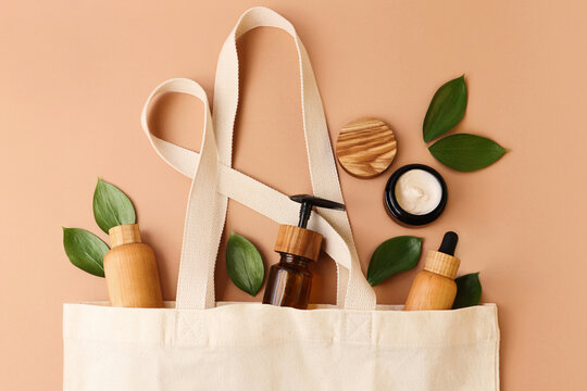 Open eco friendly cotton reusable bag with the different containers from the wood and glass.Pastel colors.Fresh natural leafs around.Concept of organic,zero waste cosmetics.Woman bag with accessories.