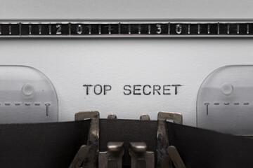Typing text TOP SECRET on vintage manual typewriter. Close up of writes word on white paper. Shot in macro. - fototapety na wymiar