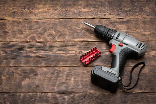 A cordless screwdriver and bits on the wooden workbench background with copy space.