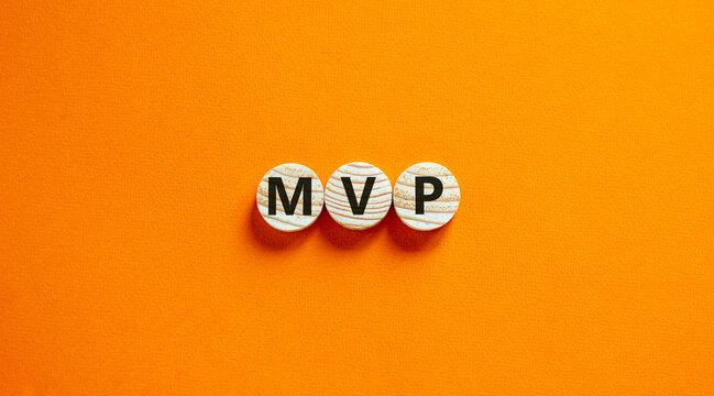 MVP, minimum viable product symbol. Wooden circles with the word MVP, minimum viable product. Beautiful orange background. Business and MVP, minimum viable product concept, copy space.