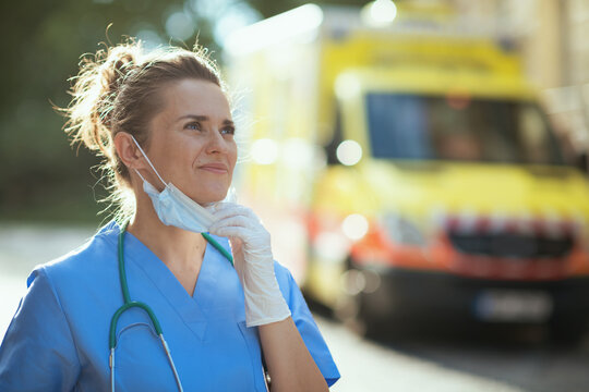 smiling medical doctor woman breathing outdoors near ambulance