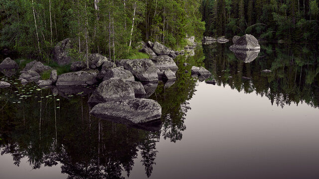 typical Finnish landscape - a lake in a pine forest with huge boulders brought here during the Ice Age. Evening, dim light, strongly diffused lighting, selective focus