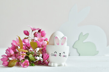 Happy Easter holiday concept with cute bunny and fresh pink flowers on white table background....
