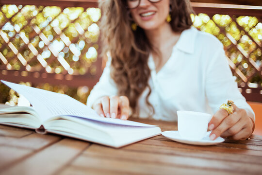 Trendy woman in shirt sitting at table reading