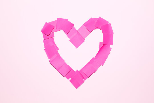 Pink Valentine's Day heart pattern. Heart shape symbol of love from blank sticky notes stuck on white wall background. Valentine's Day romantic holiday celebration office concept