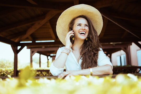 happy stylish woman in white shirt talking on smartphone