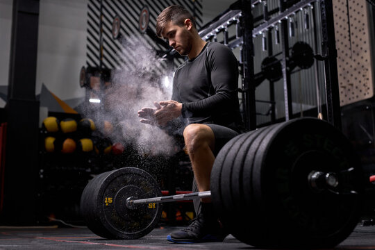 Muscular sportsman going to do squats exercise with barbell. Cross fit training in gym. Young male on sport, want to have strong powerful body, exercising with heavy weights. sport