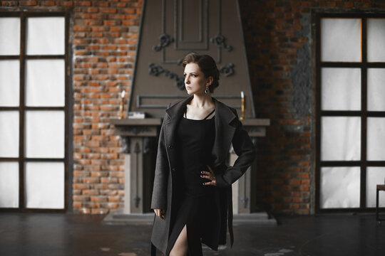 Beautiful model girl with slim body in fashionable coat posing in the vintage interior