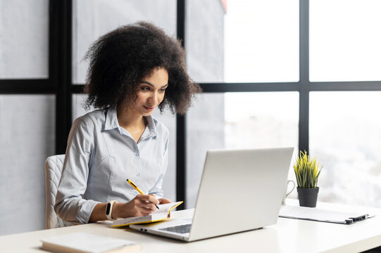 Positive African American woman studying or working in the office, sitting at the desk, using the laptop for distance video communication, watching webinar, having a meeting online, and making notes