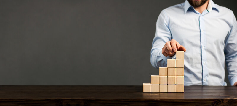 Wooden blocks cubes are stacked in ascending order on the table. Steps. Male businessman puts the top cube. Growth and construction concept.