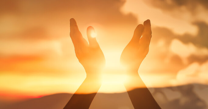 worshiping hands raised up to the sunset sky with rays of light shinning through.