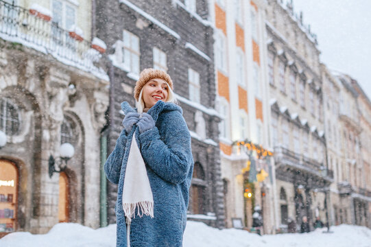 Winter, Christmas, New Year holidays, travel concept: happy smiling woman posing at street of European city. Model wearing blue faux fur coat, white scarf, beige beanie hat. Copy, empty space for text