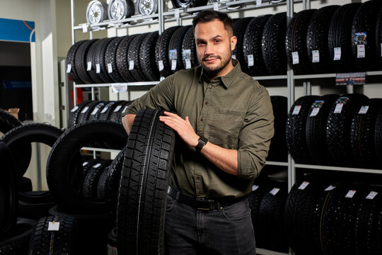 client guy stands with tires by rack of tires, he made choice, buy the best ones in auto service shop. portrait