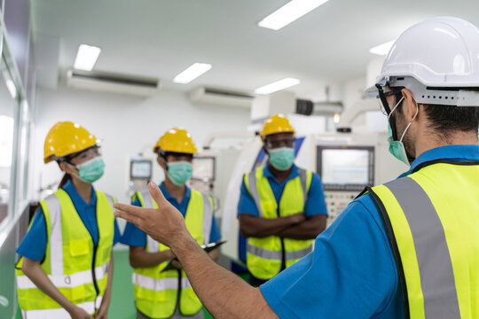Factory workers meeting before work And put on a mask