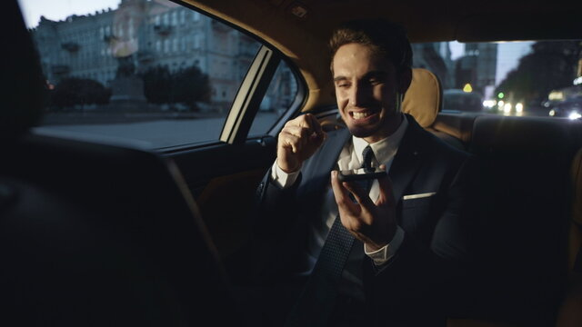 Angry business man swearing in voice chat on mobile phone in dark car.