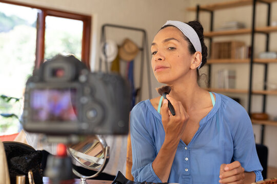 Caucasian woman, vlogging, applying makeup, using makeup brush at home