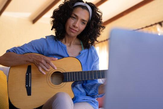 Caucasian woman playing guitar using laptop sitting on sofa at home