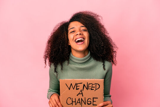 Young african american curly woman holding a we need a change cardboard laughing and having fun.