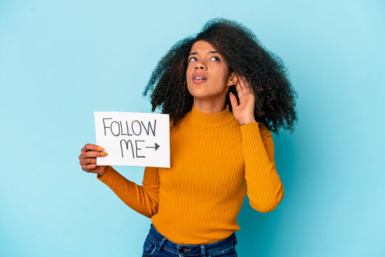 Young african american curly woman holding a follow me placard trying to listening a gossip.