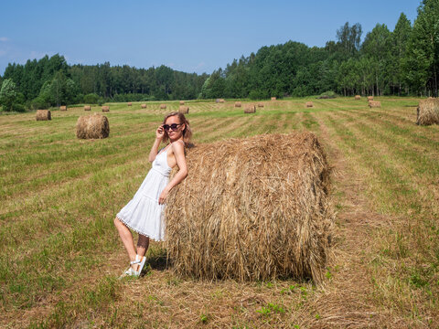 Girl in a field by a bale of hay on a summer day