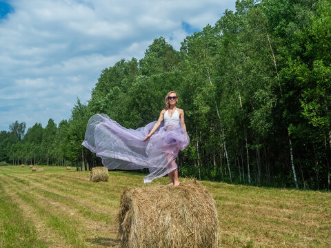 Girl dancing on a bale of hay on a summer day