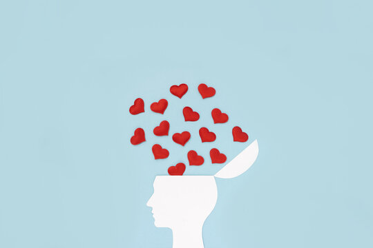 Silhouette of human's head made of white cardboard on blue background decorated with red hearts. World love thinking concept. Copy space.