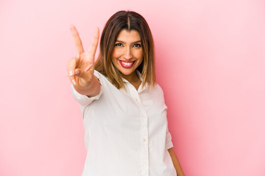 Young indian woman isolated on pink background joyful and carefree showing a peace symbol with fingers.