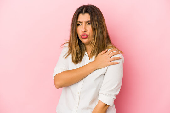 Young indian woman isolated on pink background having a shoulder pain.