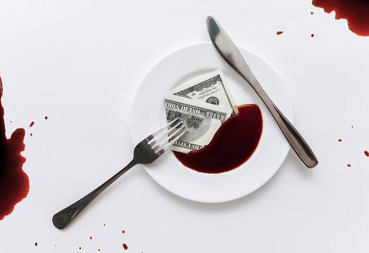 A hundred-dollar bill lies in a white plate next to blood-like soy sauce with the fork and knife on tablecloth.The concept of contracted political assassination, killer work, death-related businesses
