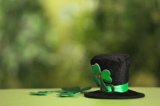 Leprechaun hat and clover leaves on table against blurred background, space for text. St Patrick's Day celebration