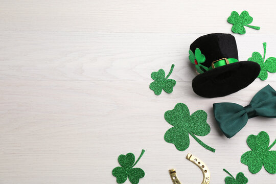 Flat lay composition with leprechaun hat on white wooden table, space for text. St Patrick's Day celebration