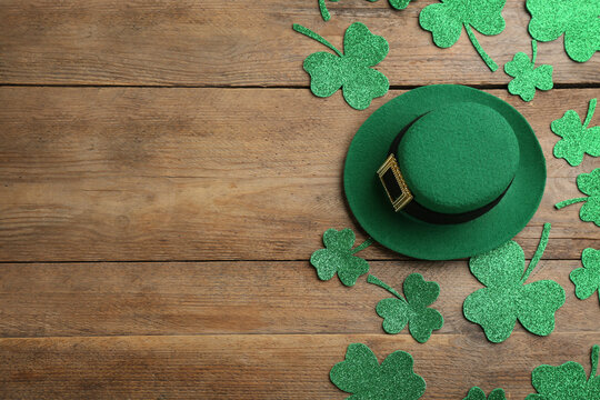 Leprechaun's hat and decorative clover leaves on wooden background, flat lay with space for text. St. Patrick's day celebration
