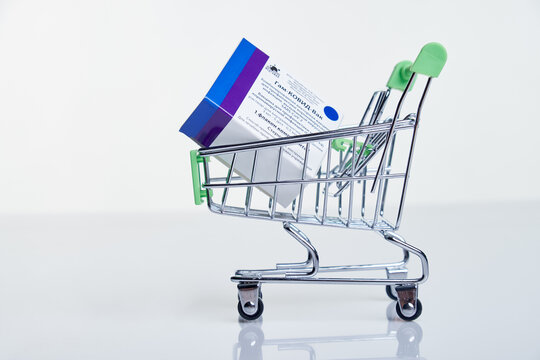 Shopping cart with Vaccine box with Sputnik V vaccine Gam-COVID-Vac on white table with reflection.