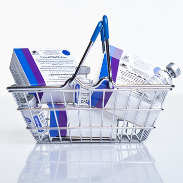Shopping basket with Vaccine boxes and vials with Sputnik V vaccine Gam-COVID-Vac on white table with reflection.